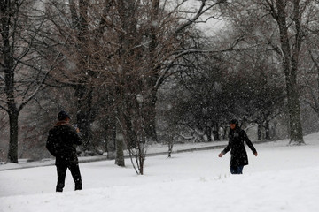 A man photographs a woman with a mobile phone in Riverside Park during a snowstorm in upper Manhattan in New York City