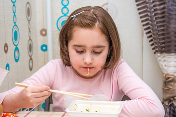 child is eating Chinese noodles with chopsticks