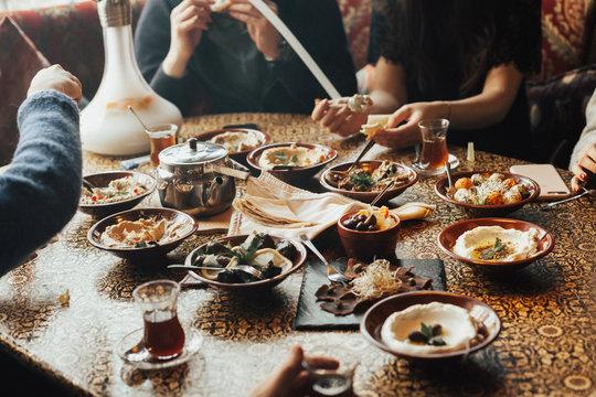 Young happy company of people is eating lebanon food and smokinh shisha. Lebanon cuisine. Traditional meze lunch