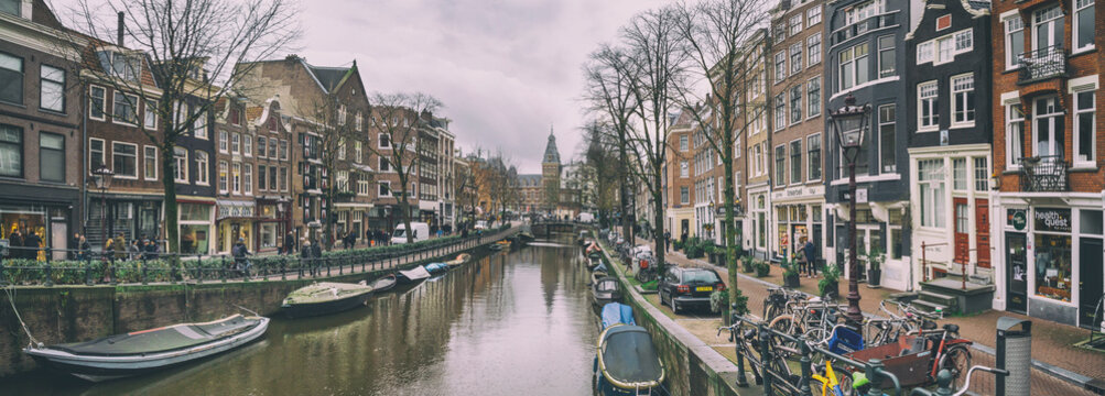 Cityscape, panorama - view of city channel with boats, city of Amsterdam, The Netherlands.