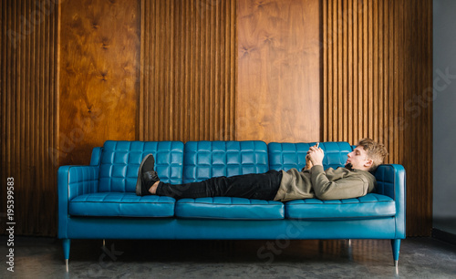 Tremendous Young Man Resting On The Couch And Looking At The Phone On A Inzonedesignstudio Interior Chair Design Inzonedesignstudiocom