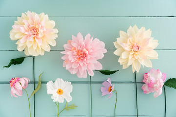 Crepe paper flowers dahlias, cosmos and echinacea on turquoise wooden background Wall mural