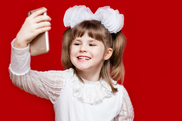 A cute little girl in white bows hold telephone and take picture on red background. Communication concept