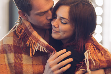 Happy woman smiling with closed eyes embraced by her man