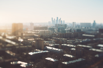 True tilt-shift view of cityscape with focus corridor going from of the shot right to the group of business skyscrapers in the distance, with strong bokeh and blur on the right and left sides of image