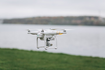 White quadrocopter is flying high in the air, taking photos, recording footage from above. Drone with four motors and propellers, camera and red warning lights.