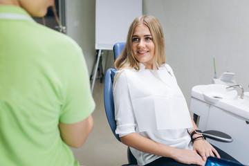 The dentist teaching a girl oral hygiene on braces in a dental clinic.