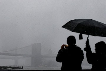 A man photographs the Brooklyn Bridge during a winter nor'easter storm in New York