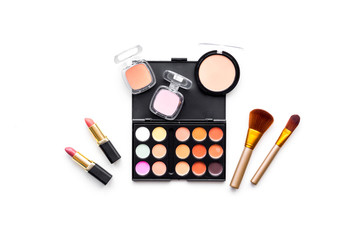Makeup background. Eyeshadow palette, rouge, powder, brushes, lipstick on white background top view copy space