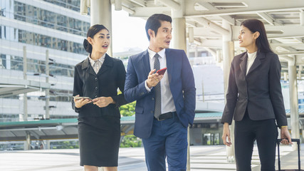 team of business people smart man and woman walk in rush hour at outdoor pedestrian walk way and talk together with tablet smart phone device and luggage with the city space building