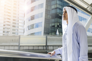 Arab man stands and look forward at outdoor city space at morning day