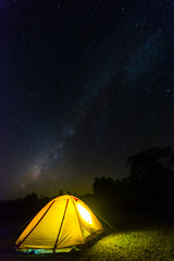 Orange tent glows under night sky.