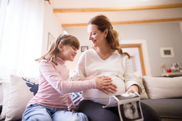 Beautiful pregnant mother and little adorable daughter cuddling a tummy while holding the ultrasound pictures of the baby.