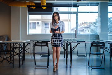 Beautiful business woman sitting on office desk and holding notebook
