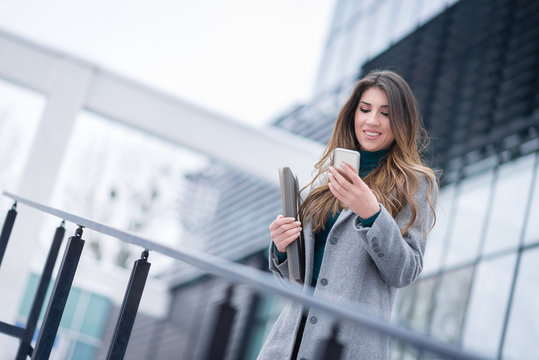 Happy young beautiful business woman holding folder and texting on smartphone in front of commercial glass building