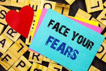 Handwritten text showing Face Your Fears. Conceptual photo Challenge Fear Fourage Confidence Brave Bravery written on colorful sticky note on the letter background Love Heart for Loving