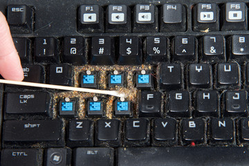 Close up filthy computer keyboard with a few keys removed, cleaning debri that has collected under keys with long cotton swab. keyboards can become clogged with food particles, dust and general grime