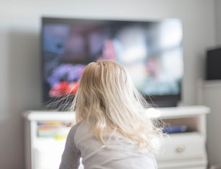 Backview of blonde child watching tv