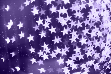 Star shaped blurred bokeh background with sparkles. Ultra violet tone, color of the year 2018
