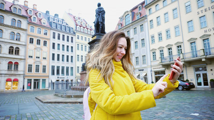 Portrait of pleasing Young woman who holds smartphone and communicates online in videocall with parents and takes pictures of architecture of old European city Dresden. Young European-looking woman