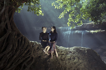 Couple two women sitting on stone under tree on waterfall backgrounds of nature in wild