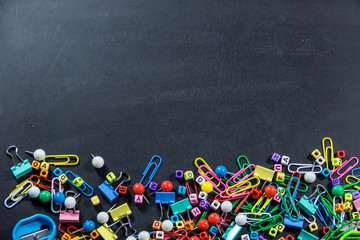 Top view of colorful office equipment with copy space on black chalkboard background. Education concept.