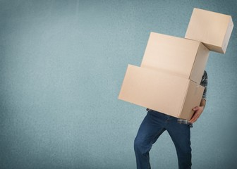 Delivery man carrying stacked boxes