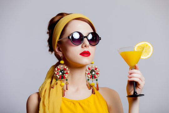 girl in 70s clothes style with tropical cocktail