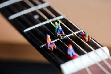 Miniature people : Child  having fun to play slider with acoustic guitar,time of relax or music relax,stationary,education concept.