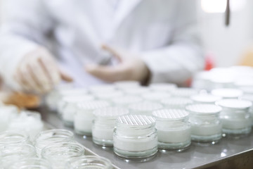 Close up picture of packing a face cream in bottles.