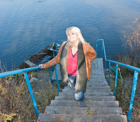 Blonde young girl by the river. Autumn Sunny day