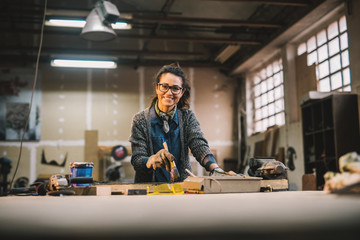 Portrait view of happy attractive hardworking middle aged professional female worker painting wood with black color in the sunny workshop or garage.