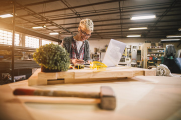 Charming smiling motivated short hair attractive middle aged industrial female engineer with eyeglasses working with blueprints and laptop in the workshop.