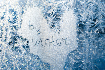 The inscription: goodbye, winter. On a frozen winter window in frosty patterns
