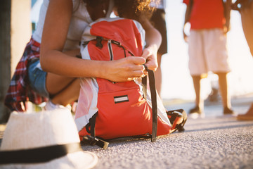 Close up view of a tourist backpack and a girl closing it