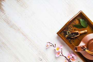 Ceramic teapot, tea leaves and sakura