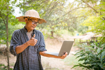 Farmer Asian with smartphone and laptop-Business and technology concept