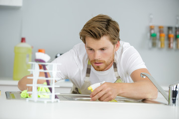 man cleaning the sink