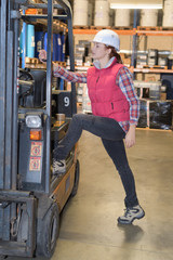 Woman stepping up into fork lift truck