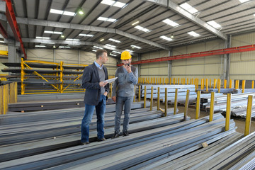 men in warehouse of metal lengths one on walkie talkie