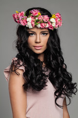 Beautiful Young Woman with Make up, Long Healthy Curly Hair and Flowers on her Head