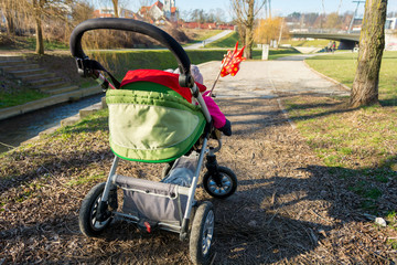 Rear view of a baby stroller with red pinwheel.