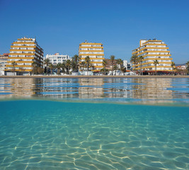 Apartment buildings on the beachfront with sand underwater, split view above and below water surface, Mediterranean sea, Spain, Costa Brava, Roses, Catalonia, Girona