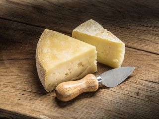 Wall Mural - Pieces of homemade cheese on the wooden background.