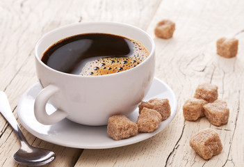 Cup of coffee and brown sugar cubes on the wooden table.