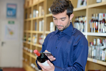sommelier scanning barcode on wine bottle through smartphone
