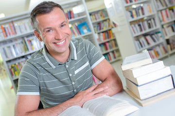 Man with books at table in library