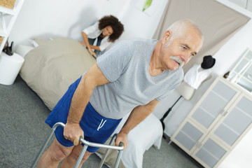 nurse assisting an elderly man with a walking frame