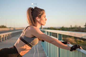 Side view portrait of beautiful sporty girl stretching over bridge's fence during morning workout outdoors.