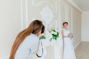 Photographer with long hair is taking pictures the young sexy bride